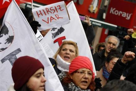 A woman holds a sign during a protest against Turkey's ruling Ak Party and PM Erdogan in Ankara